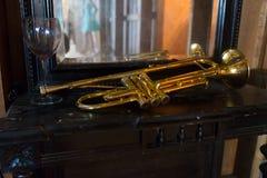 Gouden trompet die op een lijst met een glas wijn en jonge damebezinning leggen in de spiegel royalty-vrije stock foto