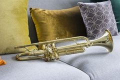 Gouden trompet die op grijze bank liggen stock fotografie