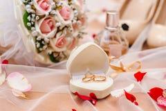 Gouden trouwringen met een boeket en een parfum stock foto