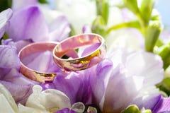 Gouden trouwringen op boeket van bloemen voor de bruid Stock Afbeeldingen