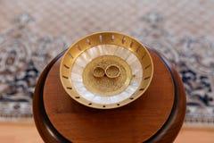 Gouden trouwringen op de tribune voor ringen Stock Fotografie