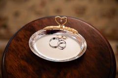 Gouden trouwringen op de tribune voor ringen Stock Foto