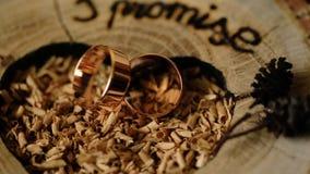 Gouden trouwringen op een houten die achtergrond voor een huwelijksceremonie wordt verfraaid stock footage