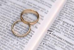 Gouden trouwringen op een pagina die liefde tonen Stock Afbeelding