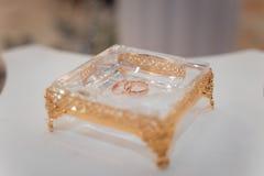 Gouden trouwringen op een tribune van glas met een gouden grens Royalty-vrije Stock Afbeeldingen