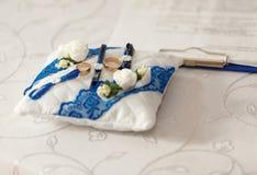 Gouden trouwringen op een wit blauw hoofdkussen Stock Foto