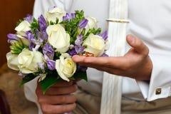 Gouden trouwringen op hand van de bruidegom Stock Afbeeldingen