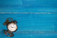 Gouden uitstekend zakhorloge gezet op een blauwe houten lijst royalty-vrije stock afbeelding