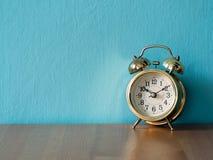 Gouden uitstekende wekker op de houten lijst de achtergrond is blauwe en exemplaarruimte voor tekst Stock Foto