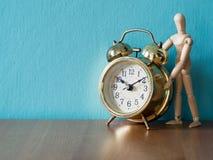 Gouden uitstekende wekker op de houten lijst in de doopvont van houten marionettentribune de achtergrond is blauwe en exemplaarru Stock Afbeelding