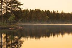 Gouden uur mooie bezinning van eiland in nevelig meer stock afbeelding