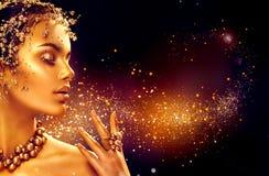 Gouden vrouwenhuid Het meisje van de schoonheidsmannequin met gouden make-up Royalty-vrije Stock Fotografie