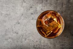 Gouden whisky in glas met ijsblokjes op lijst stock afbeeldingen