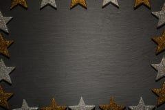 Gouden, zilveren sterren als kader op zwarte leiachtergrond Stock Afbeelding