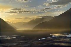 Gouden zonsondergang in de Nubra-Vallei: donkere silhouetten van hooggebergte, gouden ligh, wolken in de blauwe hemel, bij de bod Stock Foto's