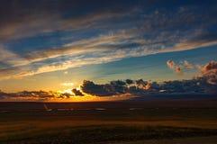 Gouden zonsopgang met kleurrijke wolken in blauwe hemel, zon omhoog op horizon als zonsondergang stock fotografie