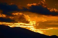 Gouden Zonsopgangzonsondergang met Gesilhouetteerde Moutnains Stock Afbeeldingen