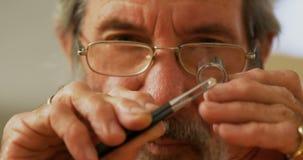 Goudsmid die vergrootglas in workshop 4k met behulp van stock footage