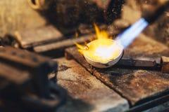 Goudsmid smeltend metaal stock afbeelding
