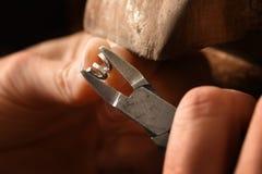 Goudsmidhanden die aan een zilveren draadspiraal werken met smal buigtang stock foto's