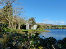 Gougane Barra Church and lake view West Cork Ireland. With blue sky and trees Royalty Free Stock Images