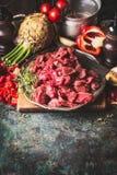 Goulache de boeuf crue de jeunes taureaux avec des légumes et des ingrédients de cuisson sur le fond rustique foncé photos stock