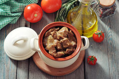 Goulash in a ceramic pot. With tomatoes, spices and rosemary on a wooden background Stock Photography