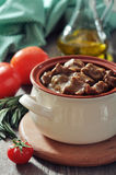 Goulash in a ceramic pot. With tomatoes, spices and rosemary on a wooden background Stock Images