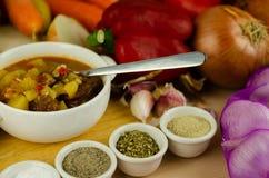 Goulash húngara tradicional com carne, batatas, tomates e pimentas, um prato saboroso em uma bacia branca foto de stock