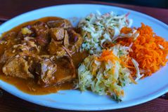 Goulash on a plate with cabbage and carrot salads and greens stock photo