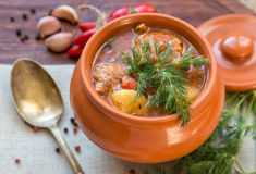 Goulash in the pot. Stew in a clay pot on a wooden board with spices Royalty Free Stock Images