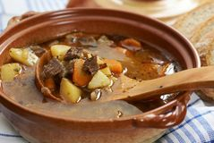 Goulash soup. Detail of bowl with goulash soup, bread and wooden ladle Stock Photos
