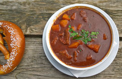 Goulash soup and pretzel at beer garden, traditional Bavarian fo Royalty Free Stock Photography