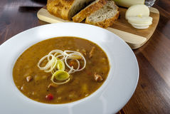 Goulash soup on wood table. With bread and onion and leek stock photography