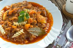 Goulash stew with potato and pasta in plate on wooden table Stock Photos