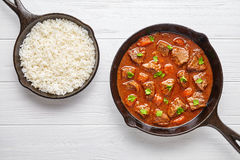 Goulash traditional Hungarian beef meat stew soup food cooked recipe with spicy gravy sauce in cast iron pan. Meal served with rice and chopped parsley on white Stock Image