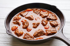 Goulash traditional Hungarian beef meat stew soup food with spicy gravy in cast iron pan royalty free stock photo