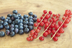 Goup of  bilberries and red currants placed on a wooden board Royalty Free Stock Image