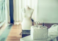 Goupilles, ciseaux et coussin de couture de goupille au-dessus d'atelier ou de studio moderne avec le simulacre Image libre de droits