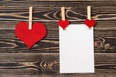 Goupilles, coeurs rouges, carte vierge sur le fond en bois Photographie stock libre de droits
