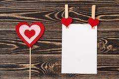 Goupilles, coeurs rouges, carte vierge sur le fond en bois Image stock