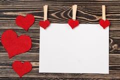 Goupilles, coeurs rouges, carte vierge sur le fond en bois Photographie stock