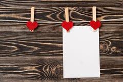 Goupilles, coeurs rouges, carte vierge sur le fond en bois Image libre de droits