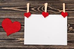 Goupilles, coeurs rouges, carte vierge sur le fond en bois Photo libre de droits