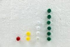 Goupilles colorées sur l'échelle de croissance d'affaires de polystyrène Photographie stock libre de droits