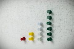 Goupilles colorées sur l'échelle de croissance d'affaires de polystyrène Photos stock