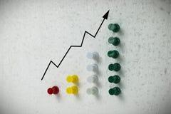 Goupilles colorées sur l'échelle de croissance d'affaires de polystyrène Photographie stock
