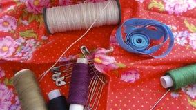 Goupilles d'aiguilles de fil sur le tissu rouge Photo libre de droits
