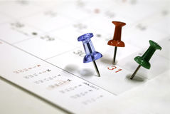 Goupilles de vert de rouge bleu sur un calendrier Photos libres de droits