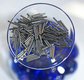 Goupilles en métal dans un bol en verre Photos stock